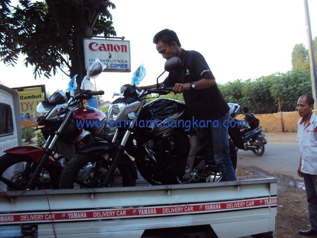 Dua Orang Petugas Sedang menurunkan Motor Yamaha Byson Warna Hitam